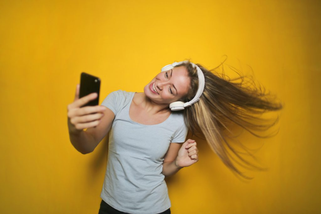 Image of a girl with headphones on, looking at her phone, on a yellow background