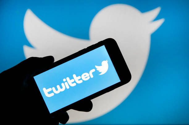 Twitter logo on a mobile against a Twitter logo background